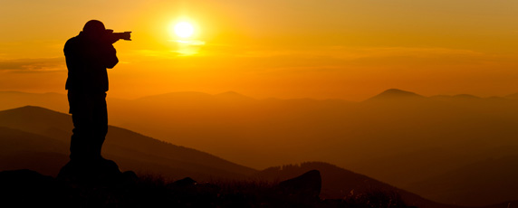 Pohled na siluetu fotografa na vrcholcích kopců, který fotí slovenskou krajinu při západu slunce.