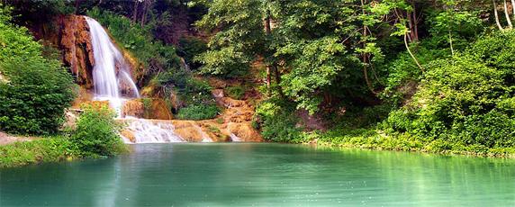 Pohľad na jazierko s vodopádom odfotografované tesne po letnej búrke v obci Lúčky na Slovensku.